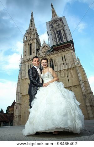 Newlyweds Holding Hands In Front Of Cathedral