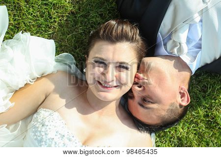 Newlyweds Kissing On Grass