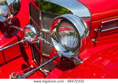 Red detail on the headlight of a vintage car