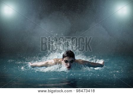 Swimmer in waterpool, butterfly style