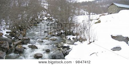 Wild Small River In The Mountains With Snow On The Banks And A French Chalet On The Right, Les Menui