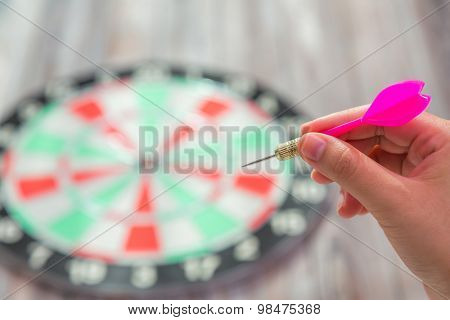 Hand holding red arrow and throwing to dart board
