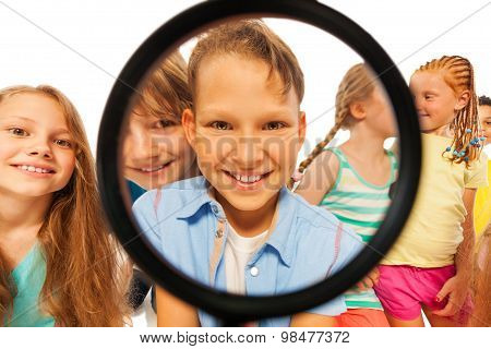 Boy through magnifier glass and with friends