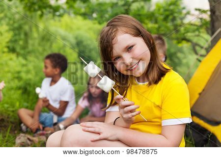 Beautiful girl holding marshmallows near tent
