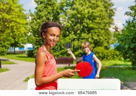 African girl playing ping pong with boy outside