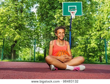 Smiling African girl sits on playground with ball