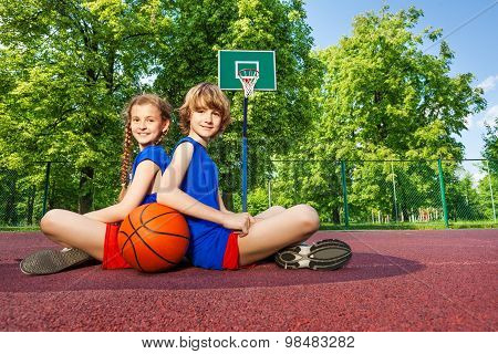Boy and girl sit with backs close on playground