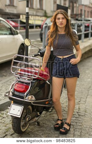 Attractive young girl standing in the european town near his motorbike.