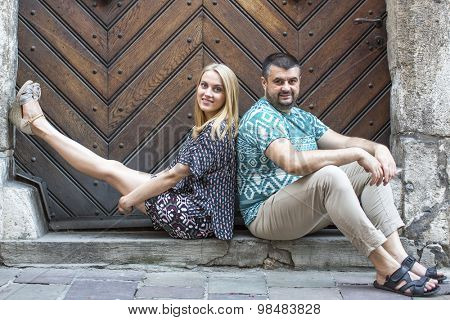 Young couple sitting on the threshold of old wooden doors.