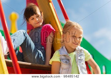 summer, childhood, leisure, friendship and people concept - happy kids on children playground climbing frame