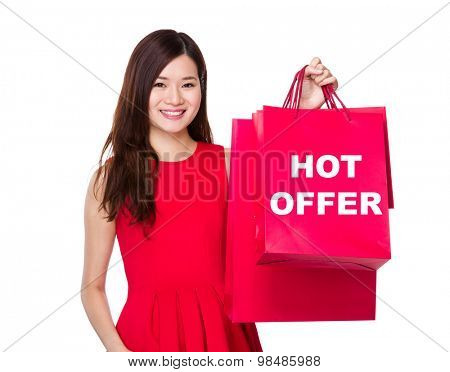 Woman hold with paper bag and showing hot offer