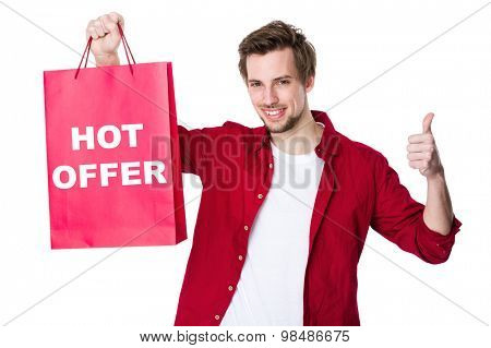 Happy man shopping with his thumbs up and showing hot offer