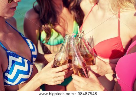 summer vacation, holidays, party, travel and people concept - close up of happy young women with drinks clinking bottles on beach