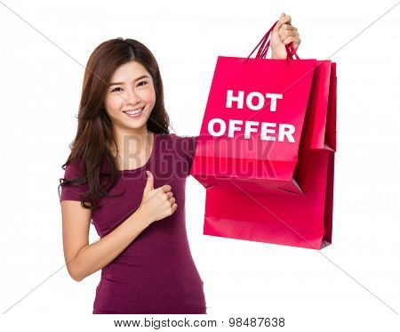 Happy shopping young woman with thumb up gesture and holding bag showing hot offer