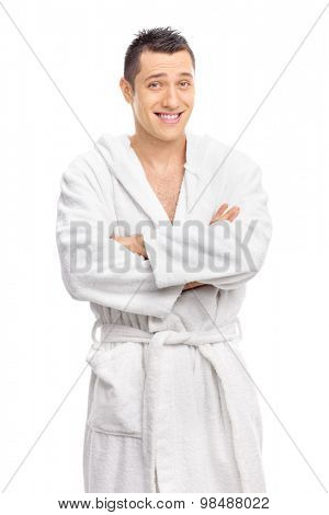 Vertical shot of a cheerful young guy posing in a white bathrobe isolated on white background