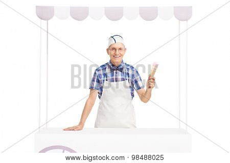 Studio shot of an ice cream vendor holding an ice cream cone and posing behind a stall isolated on white background