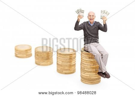 Studio shot of an overjoyed senior holding a lot of money seated on a stack of coins isolated on white background