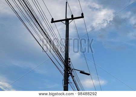 Electricity post And wires backlit the sky