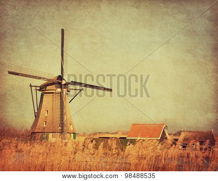 View of windmill at Kinderdijk, Netherlands. Photo in retro style. Added paper texture. Toned image
