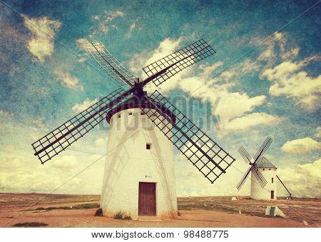 Retro image of Medieval Windmills. Castilla La Mancha, Spain. Added  Paper texture. Toned image