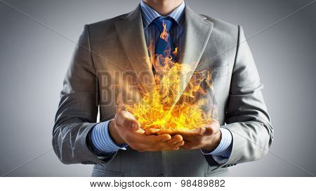 Young businessman holding fire flames in palms