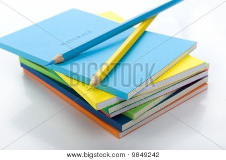 two colored pencils at the top the stack of books