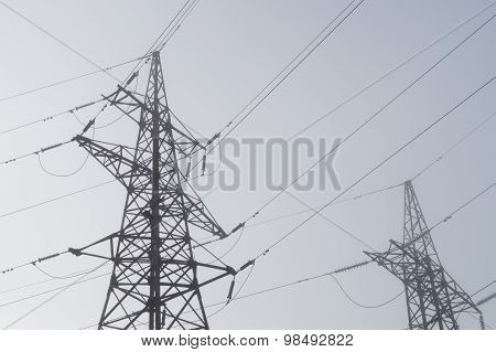 Electric High Voltage Power Towers At Morning Mist