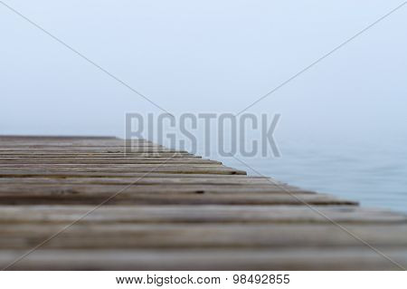 Abstract Blurred View Of Misty Lake With Selective Focus On Wooden Pier