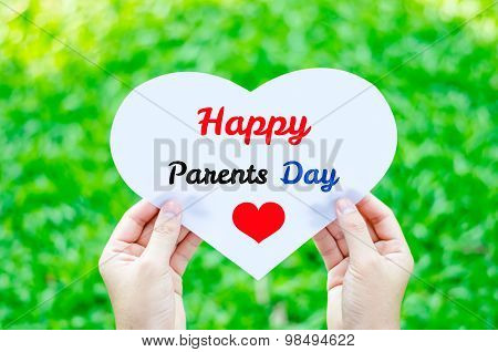 Hand Holding White Heart Paper With Happy Parents Day Text On Blur Green Grass Background