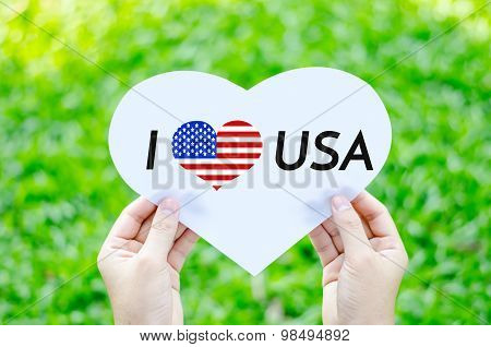 Hand Holding White Heart Paper With I Love Usa Text On Blur Green Grass Background