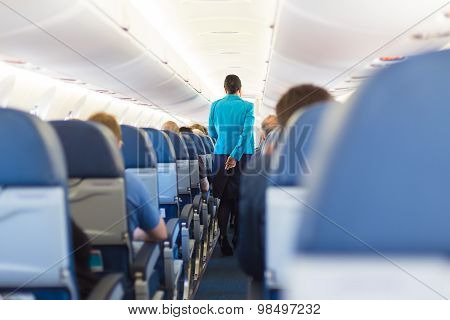 Interior of airplane with stewardess walking the aisle.