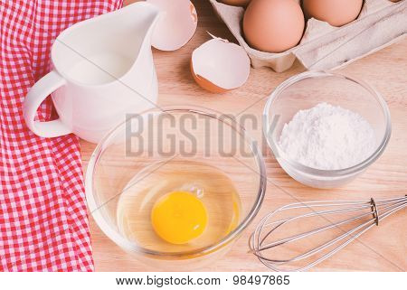 Cookies ingredients. Bowl, flour, eggs, jar of milk, eggbeater,eggshells and red napkin