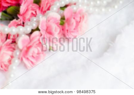 Blur Pink Carnation Flower Background With Pearl Necklace And White Fur With Place For Text