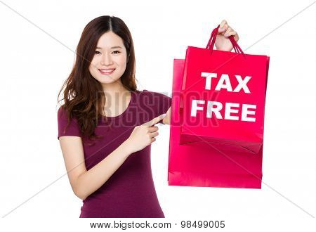 Asian woman with finger point to shopping bag and showing tax free