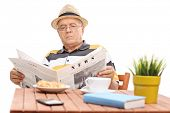 Постер, плакат: Mature man reading a newspaper seated at a coffee table with few croissants on it The newspaper is c