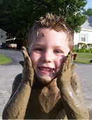 picture of mud pack  - young boy covered with mud applying more to the sides of his face - JPG