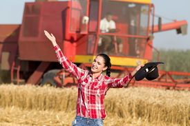 pic of cowgirl  - Pretty cowgirl with hat and raised arms in the golden wheat field combine harvester in background - JPG