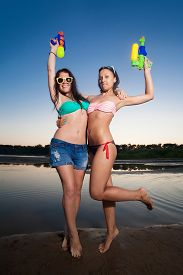 foto of pistols  - Two young girl posing with water pistols - JPG