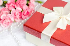 stock photo of carnations  - Close up of gift box with pearl necklace and pink carnation flower on white fur background - JPG