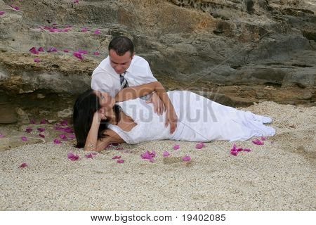 Just Married - bride in groom's arms on the beach and bed of flowers