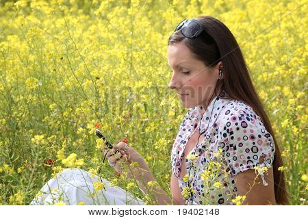 pretty young woman with mobile phone and earphones on a meadow