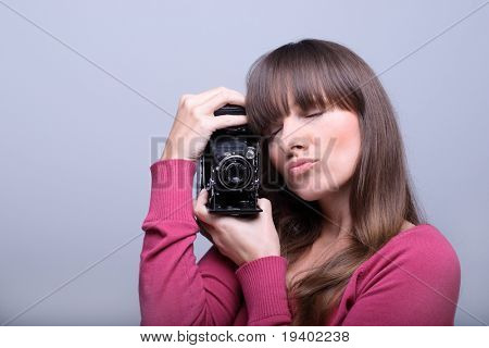 Young beautiful  woman holding a vintage photo camera