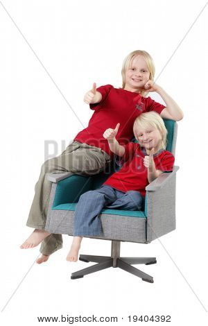Two cute young boys with blind hair sat on armchair with thumbs up; white studio background.