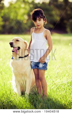 Young girl standing in long grass with a golden retriever