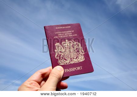 Holding A British Passport In Front Of A Blue Sky.