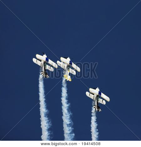 Three aerobatic aeroplanes flying straight up during an airshow