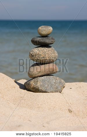 Six differently colored and sized pebbles stacked on a beach