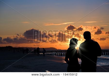Silhouette of couple talking on a beach shore in sunset light
