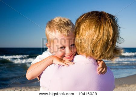 3 years old boy hugging his mother on a beach in sunny day