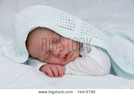 Newborn boy covered by blue blanket sleeping
